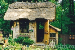 Whimsical Cordwood Thatched Potting Shed with Rabbit Hutch on Side