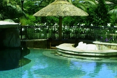 Custom Thatch Umbrella in a Backyard Oasis with Pool and Cave